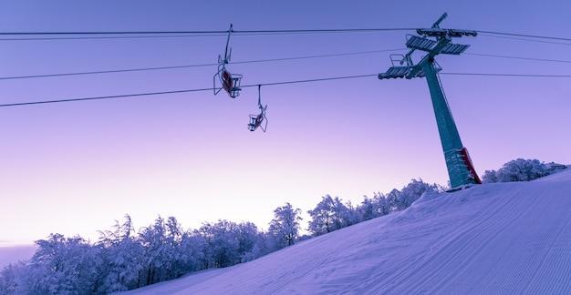 Vacanze invernali nella stazione sciistica di montagna. il supporto dell'ascensore è coperto di neve e brina all'alba. meraviglioso paesaggio al tramonto.