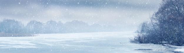 Vista invernale con ghiaccio e fiume coperto di neve e alberi lungo il fiume durante le precipitazioni nevose. sfondo di natale