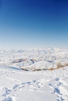 Vista invernale dalle pendici della montagna di beldersay in tempo sereno soleggiato con cieli blu