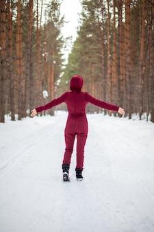 Passeggiata invernale in una foresta innevata, una ragazza con una tuta rossa e una giacca cammina tra alberi ad alto fusto nella natura.