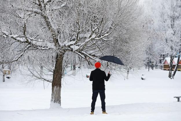 Passeggiata invernale con un ombrello. uomo con un cappotto con un ombrello, cammina sullo sfondo del paesaggio invernale, vista invernale
