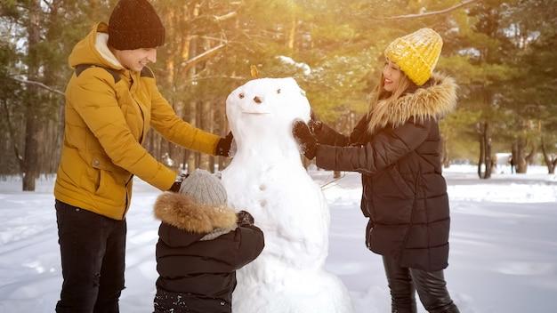 Passeggiate invernali e giochi con il bambino nel fine settimana. la mamma, il papà e il figlio della famiglia felice stanno costruendo insieme un pupazzo di neve nel parco invernale.