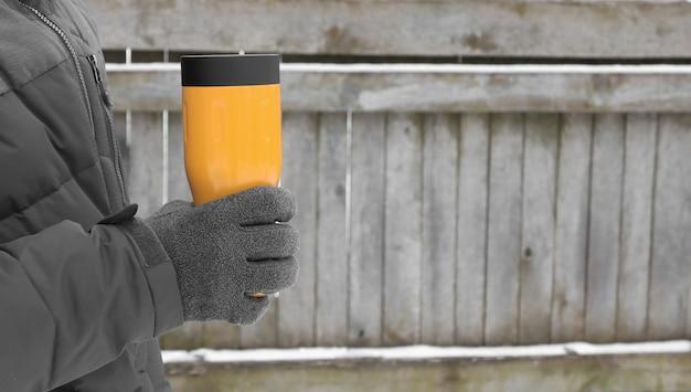 L'inverno cammina per strada nel parco bevanda calda in un thermos
