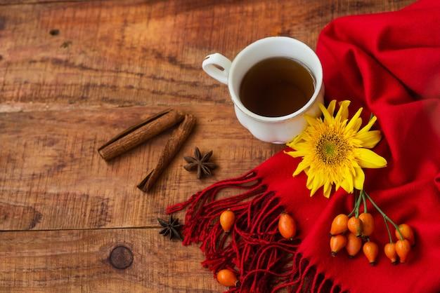 Inverno, atmosfera calda. tazza di tè nero caldo con sciarpa rossa, bastoncini di cannella, bacche di rosa e girasole su fondo di legno. serata d'inverno. disposizione piatta, layout, posto per testo, cartolina
