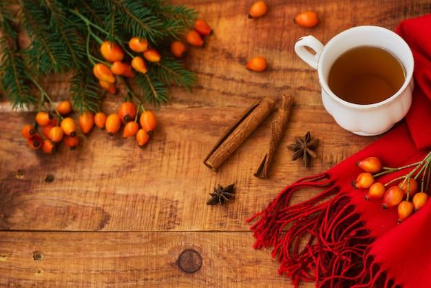 Inverno, atmosfera calda. tazza di tè nero caldo con sciarpa rossa, bacche di rosa, bastoncini di cannella e abete rosso su fondo di legno. serata d'inverno. disposizione piatta, layout, posto per cartoline di testo, alta risoluzione