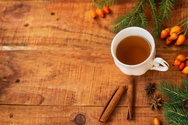 Inverno, atmosfera calda. una tazza di tè nero caldo con le bacche di rosa, i bastoncini di cannella e l'abete rosso su uno sfondo di legno. serata accogliente d'inverno. disposizione piatta, layout, posto per il testo, alta risoluzione