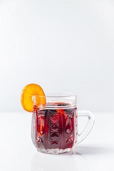 Riscaldamento invernale vin brulè in tazza di vetro su uno sfondo bianco.