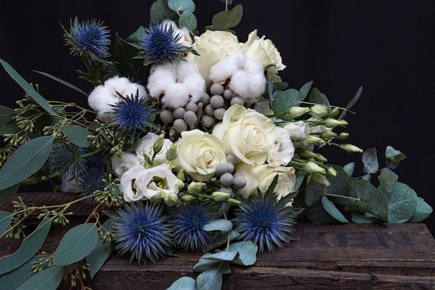 Bouquet da sposa invernale di rose bianche, cotone ed eringium su fondo nero. il bouquet della sposa.