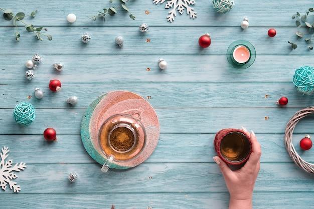 Tè invernale, disposizione con teiera in vetro, bicchiere di tè in mano. decorazioni natalizie, palline, giocattoli, candele da tè ed eucalipto.