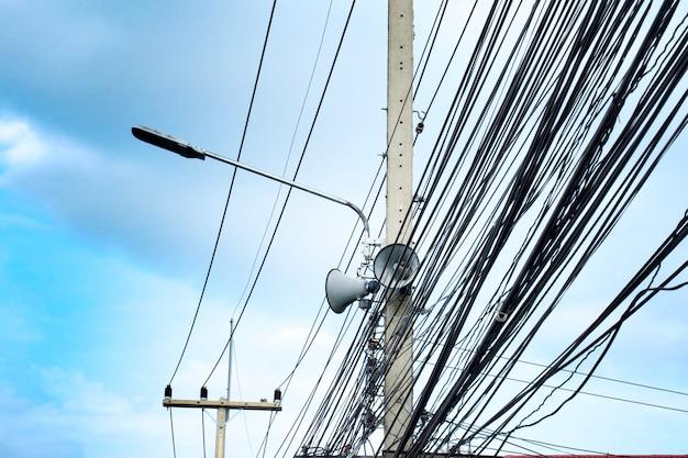 Cavo, lampada fluorescente ed altoparlante sul palo elettrico in tailandia con cielo blu.