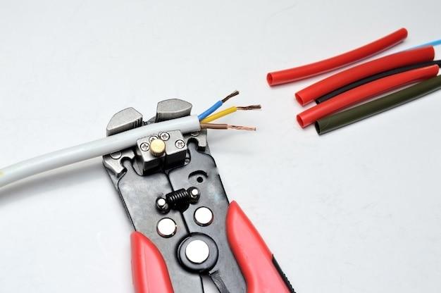 Spellafili, cavo schermato a tre conduttori e guaina termorestringente su sfondo bianco. avvicinamento