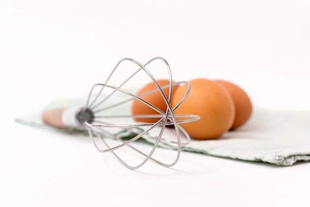 Frusta a filo e uova di gallina crude su un canovaccio da cucina. strumento manuale per mescolare gli ingredienti per la cottura