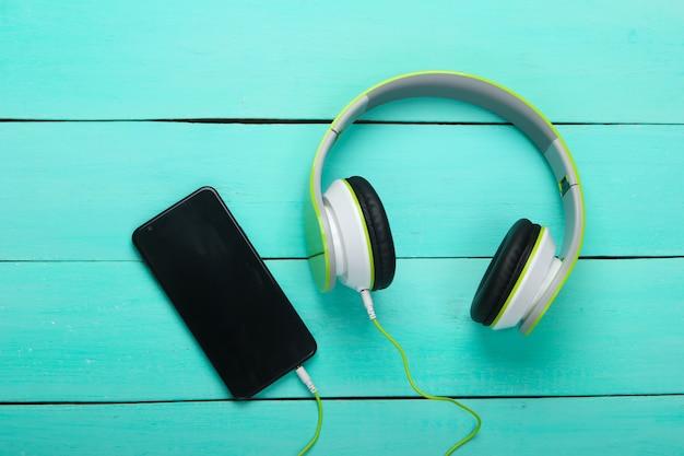 Cuffie stereo cablate con smartphone sulla tavola di legno blu Foto Premium
