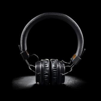 Cuffie wireless nere sull'orecchio su sfondo ardesia scuro