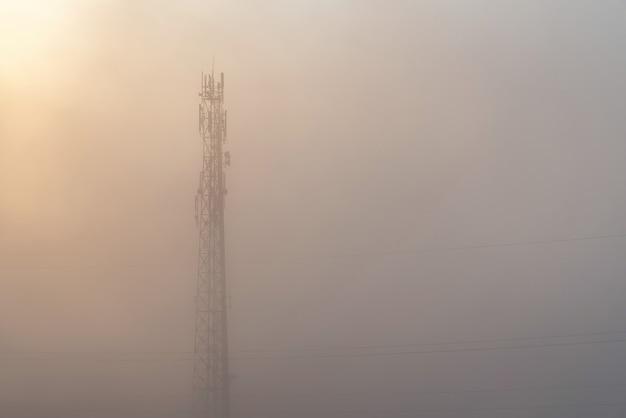 Torre di rete mobile di comunicazione wireless circondata da una fitta nebbia visibilità zero