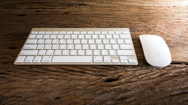 Tastiera di computer senza fili con l'alfabeto inglese e tailandese e il mouse sulla tavola di legno