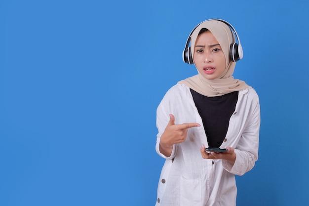 Connessione senza fili. ritratto di giovane donna in posa isolato su musica d'ascolto blu