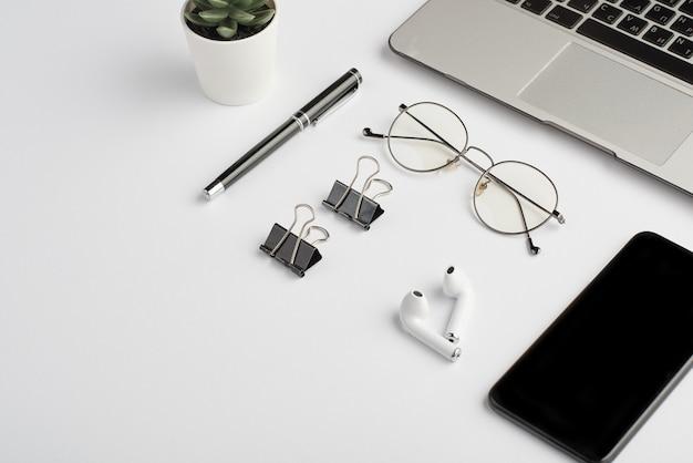 Auricolari wireless, occhiali da vista, penna, clip, telefono cellulare e tastiera portatile sulla scrivania bianca che è il posto di lavoro del dipendente