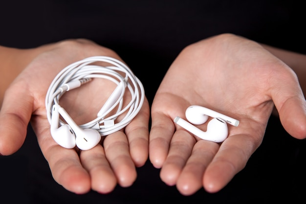 Auricolari senza fili sulle mani umane. girato in studio.