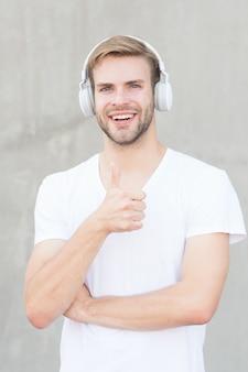 Auricolare senza fili. bel ragazzo indossare cuffie sfondo grigio. l'uomo ascolta musica moderna. tecnologia moderna. musica moderna e contemporanea. tempo libero per hobby. cuffie stereo pieghevoli. riduzione del rumore.
