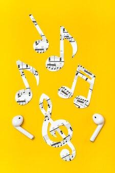 Cuffie wireless e note musicali tagliate da carta su una superficie gialla. concetto di imitazione musicale. vista verticale