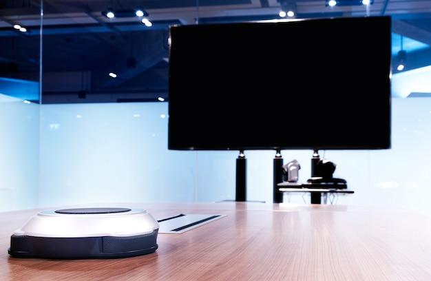 Microfono wireless portatile sul tavolo con televisore a schermo vuoto nella sala riunioni