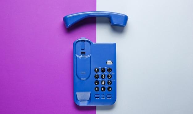 Telefono senza fili dell'ufficio con il microtelefono sulla tavola grigia porpora.