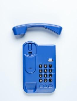 Telefono senza fili dell'ufficio con un tubo su una tavola bianca