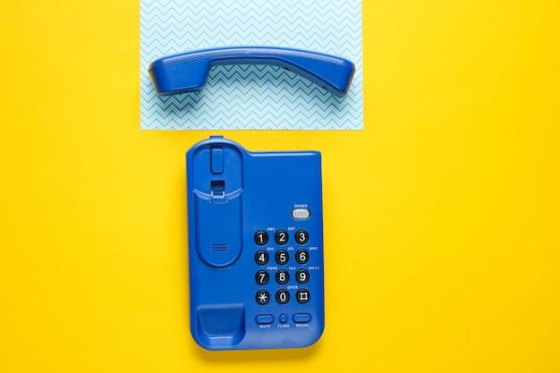 Telefono senza fili dell'ufficio con un tubo sulla tavola gialla