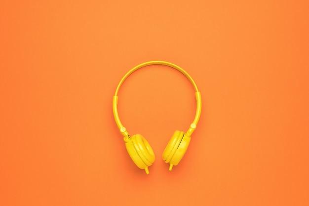 Cuffie senza fili gialle su uno sfondo arancione brillante. un accessorio elegante per ascoltare la musica.