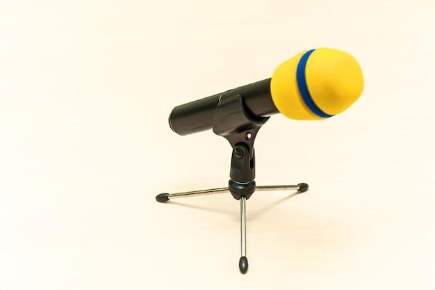 Microfono giallo senza fili con supporto su tavolo bianco per parlare oratori in conferenza