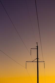 Fili sulle linee elettriche che vanno verso il tramonto