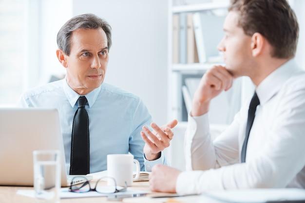 Consigli saggi per affari piacevoli. due uomini d'affari in abiti da cerimonia che discutono di qualcosa