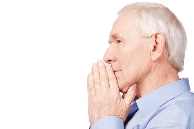Saggio e fiducioso. vista laterale della camicia da uomo anziano che tiene le mani giunte e distoglie lo sguardo mentre è seduto su una sedia nel suo appartamento