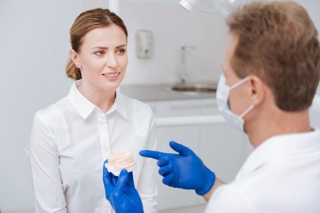 Saggio fantasioso dentista locale che utilizza un modello speciale per dimostrare come sta andando a riparare il suo sorriso paziente