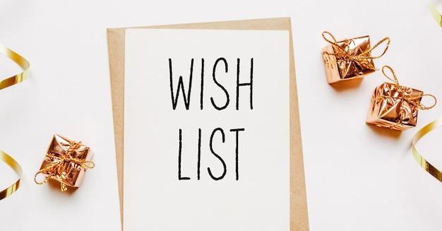 Nota della lista dei desideri con busta, regali e nastro d'oro su sfondo bianco. buon natale e anno nuovo concetto