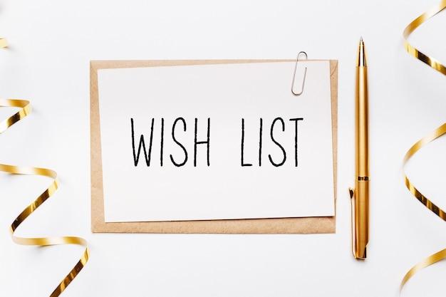 Lista dei desideri nota con busta, penna, regali e nastro d'oro su sfondo bianco. buon natale e capodanno concept