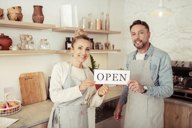 Auguri di benvenuto. i proprietari sorridenti di una bella caffetteria di famiglia salutano i loro primi visitatori.