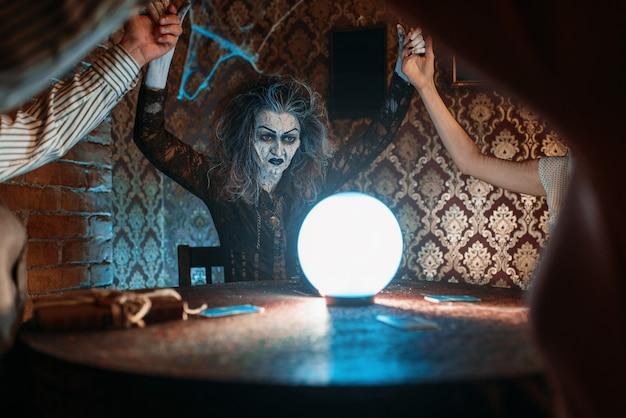 Strega su una sfera di cristallo, giovani in seduta spiritica