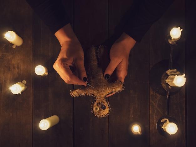 Una strega nell'oscurità tiene in mano una bambola di pezza voodoo circondata da candele, piatta.