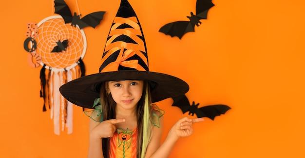 Strega di halloween che punta con le dita da parte nello spazio della copia su uno sfondo arancione per studio