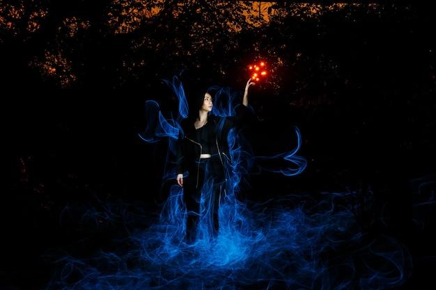 Strega che gioca con le luci come il fuoco nella foresta durante halloween