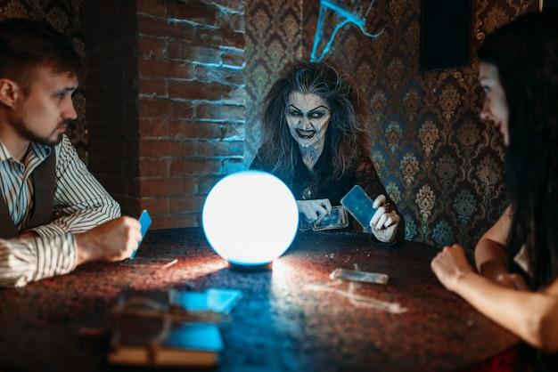 La strega legge un incantesimo magico su una sfera di cristallo
