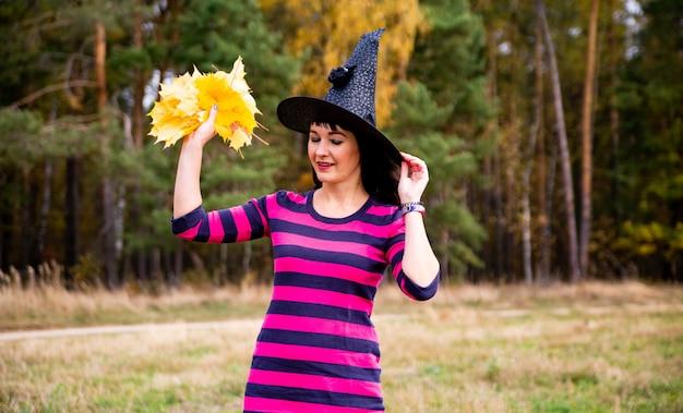 La strega lancia le foglie nella foresta autunnale. halloween festa in costume mago donna