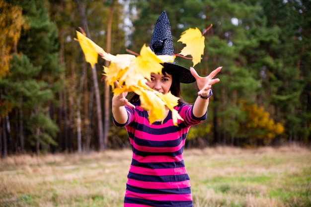 Strega lancia foglie nella foresta autunnale mago festa in costume di halloween