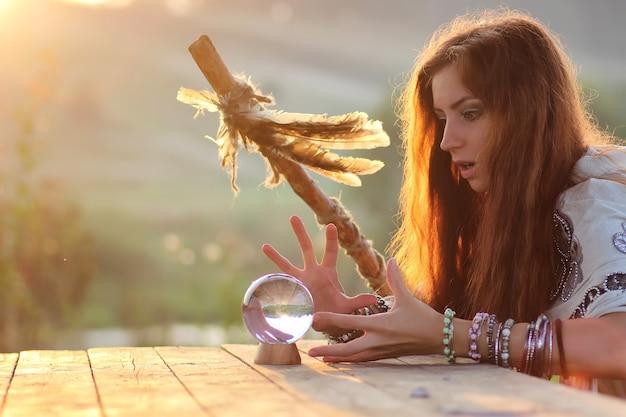 Strega con sfera di cristallo al tramonto