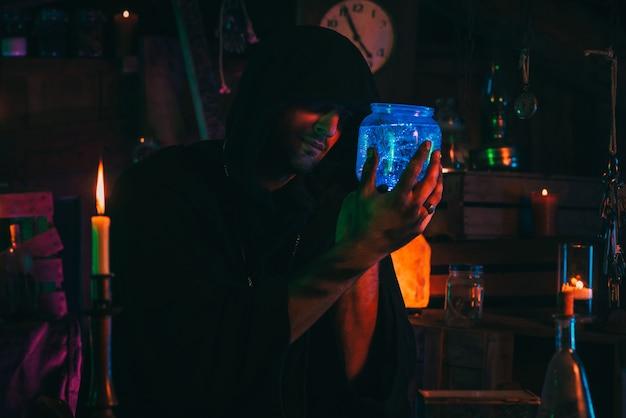 L'alchimista witcher crea una pozione segreta nel cupo laboratorio del laboratorio. mago oscuro stregone in costume di halloween a tavola