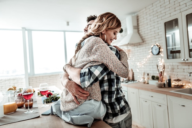 Con l'amato marito. donna sottile abbastanza bionda con orecchini enormi che si sente meravigliosa mentre abbraccia il suo bel marito