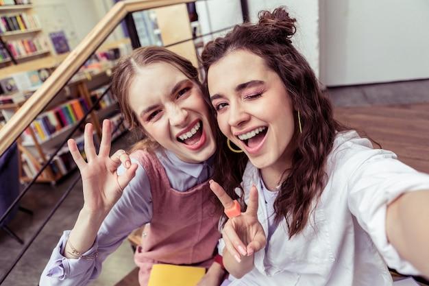 Con una pelle impeccabile. accattivanti donne gesticolano attivamente durante i selfie per i social media mentre mostrano le dita e fanno l'occhiolino