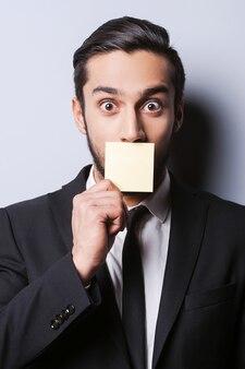 Con umorismo alle offerte. ritratto di un giovane sorpreso in abiti da cerimonia che si copre la bocca con la nota adesiva mentre si trova su uno sfondo grigio
